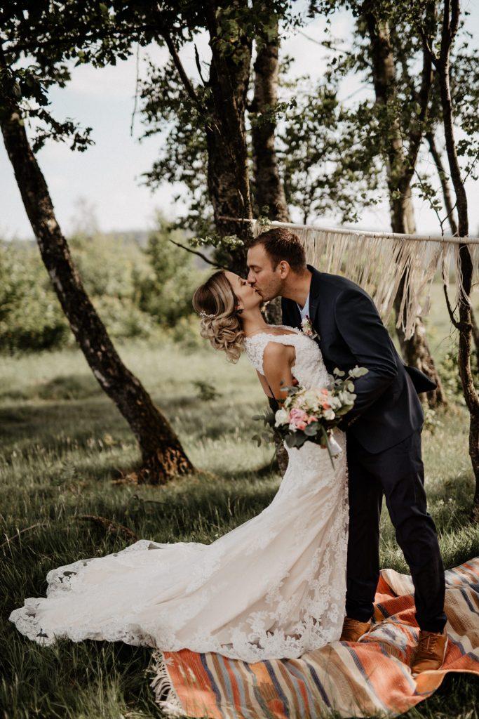Bräutigam küsst seine Bohobraut vor einem Makramee Hintergrund