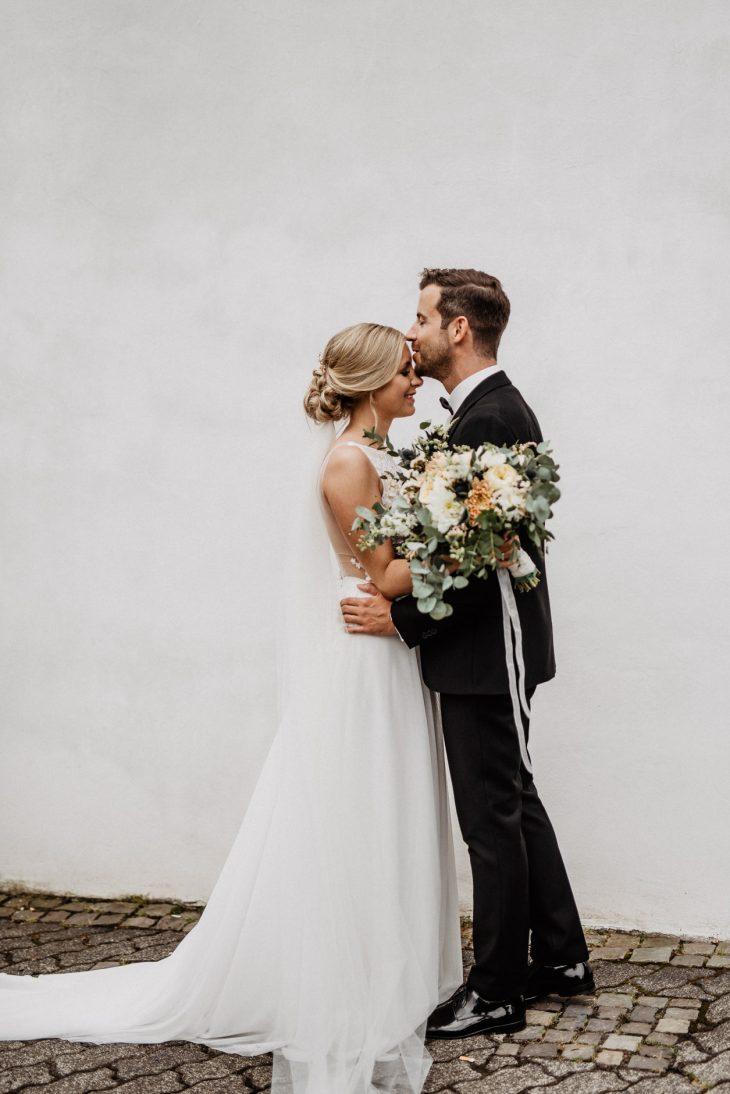 Bräutigam küsst seine Bohobraut liebevoll auf die Stirn
